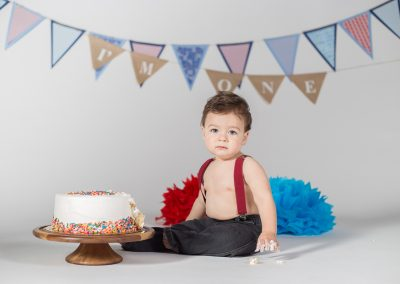 Baby boy in jeans in suspenders with smash cake in Alpharetta