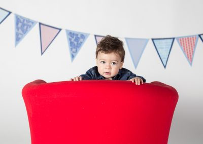 One Year Old Boy Peeking over the back of Red Chair during Milestone Photography Session