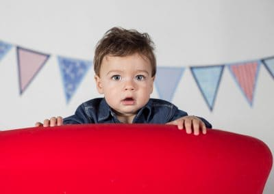 One Year Old Boy Peeking over the back of Red Chair