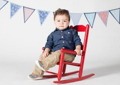 Baby Boy Sitting in Red Rocking Chair in Alpharetta Studio