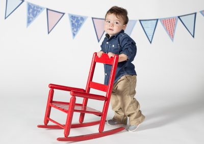 Baby Boy Standing by Red Rocking Chair in Alpharetta Studio
