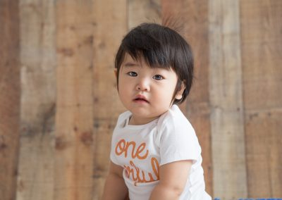 "Baby Girl wearing a ""One derful"" onsie in a Suwanee Studio"