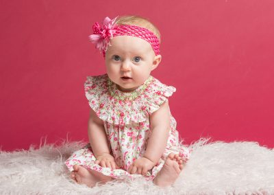 Baby Girl in Floral dress and pink bow sitting on light pink rug