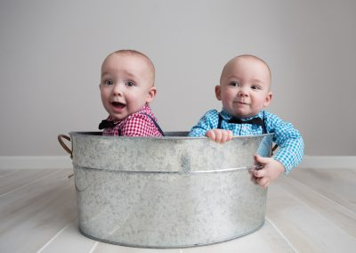 One Year Old Twin Boys sitting in metal tub