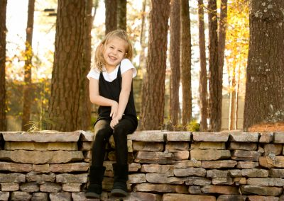 Young grinning girl sitting on stack stone wall in Alpharetta