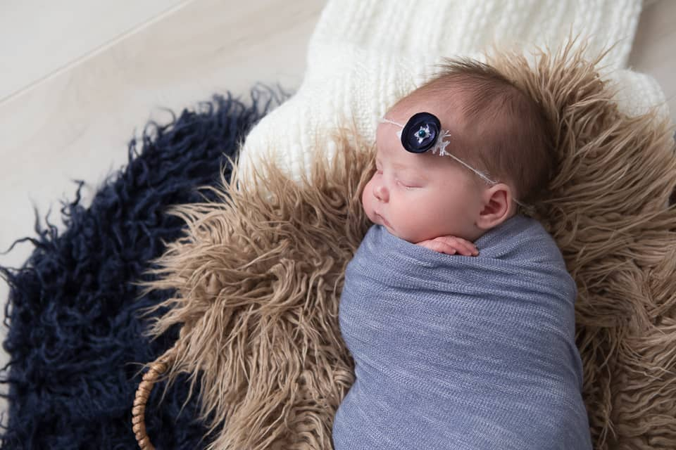 Newborn baby girl in blue, navy, cream, and tan. Photo by Colleen Hight Photography.