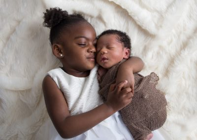 Newborn Boy snuggled with Big Sister on Cream Blanket in Suwanee newborn studio
