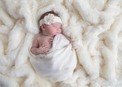 Baby girl on cream colored background for newborn session.