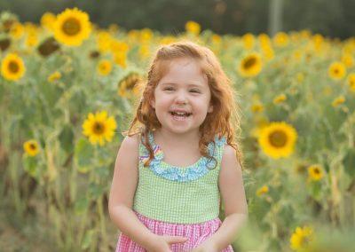 Red-headed girl laughing in a sunflower field in Cumming, Georgia