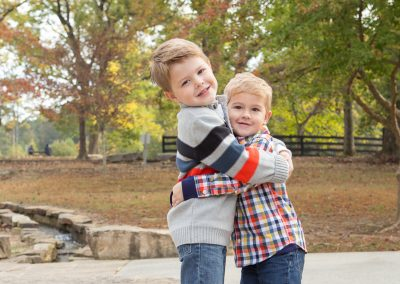 Two boys smiling and hugging each other in a Suwanee, Georgia Park