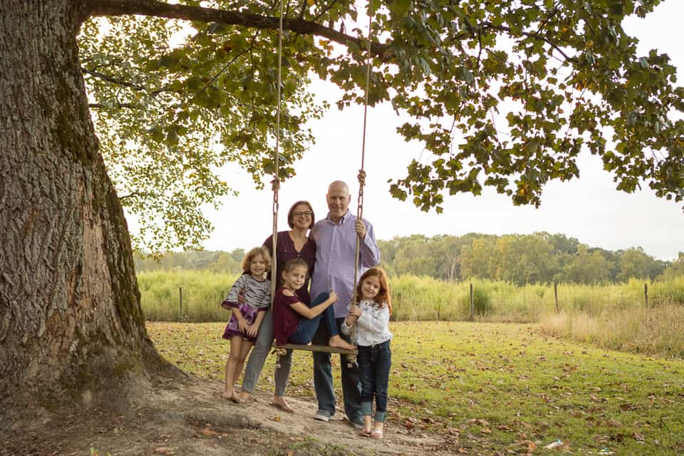 Family with two sons and young daughter in field in front of haystack in Lawrenceville, Georgia
