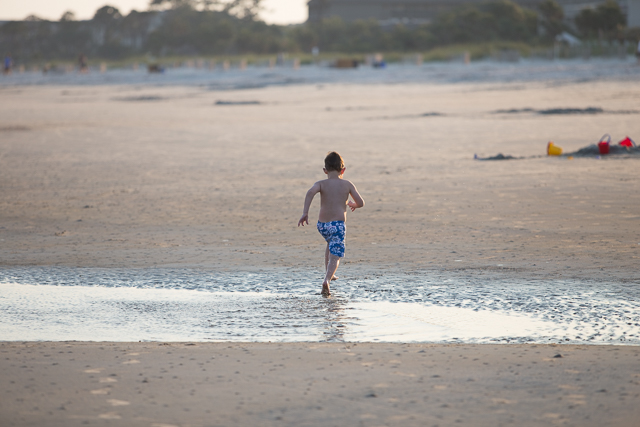 Boy running away through standing water on Hilton Head Island Beach