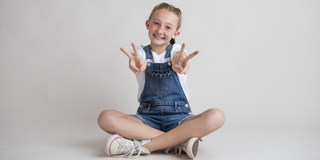 Girl showing peace signs during headshot portraits in Suwanee, Georgia