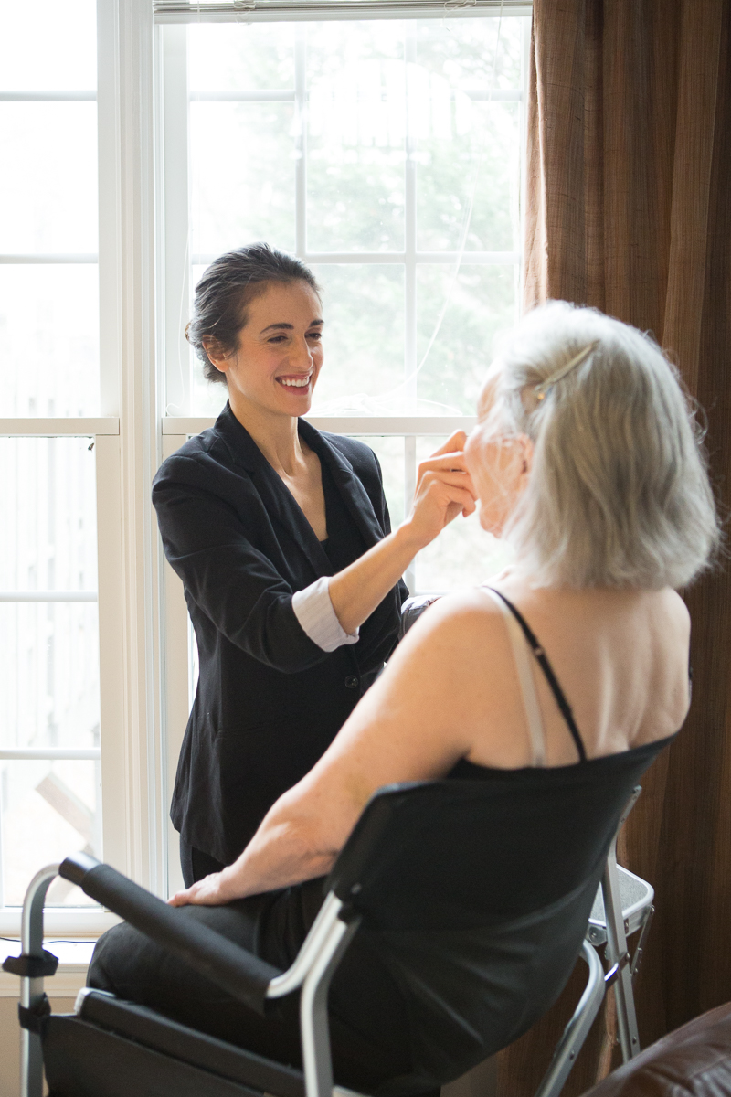 Hair and makeup artist smiling while applying makeup on client