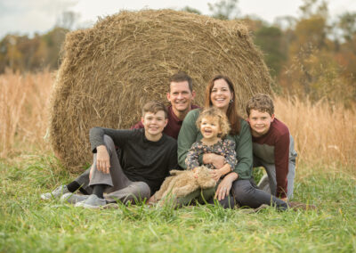Family in Lawrenceville, Georgia field in front of haystack