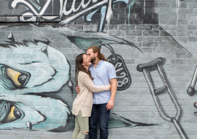 Couple laughing together in front of Atlanta graffiti wall
