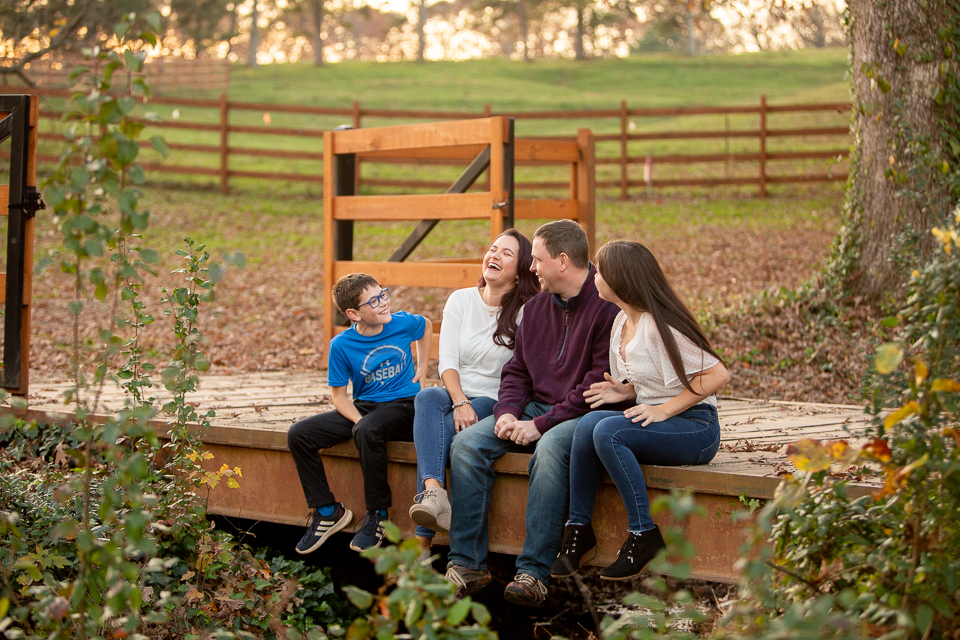Family sitting on bridge laughing together in Mabry Park in Marietta, Georgia