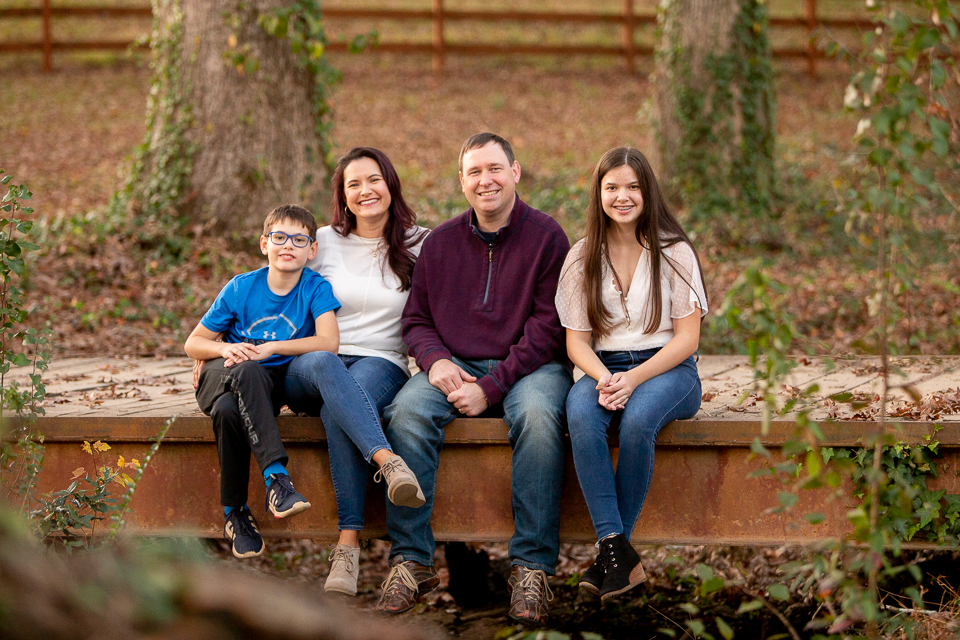 Family fo four with son and daughter sitting on bridge in Marietta park