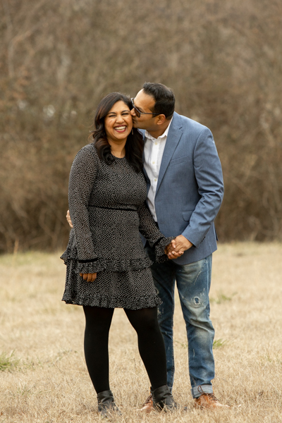 Husband kissing wife in field during family photo session in Suwanee, Georgia