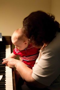 Grandma showing baby how to play piano